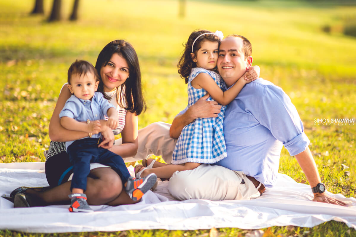 Family posing for picture sitting on the ground grass