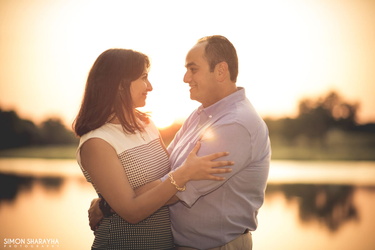 man and wife looking at each other front of the sun and lake