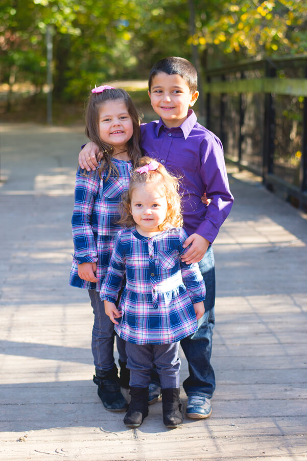 three kids standing and posing together
