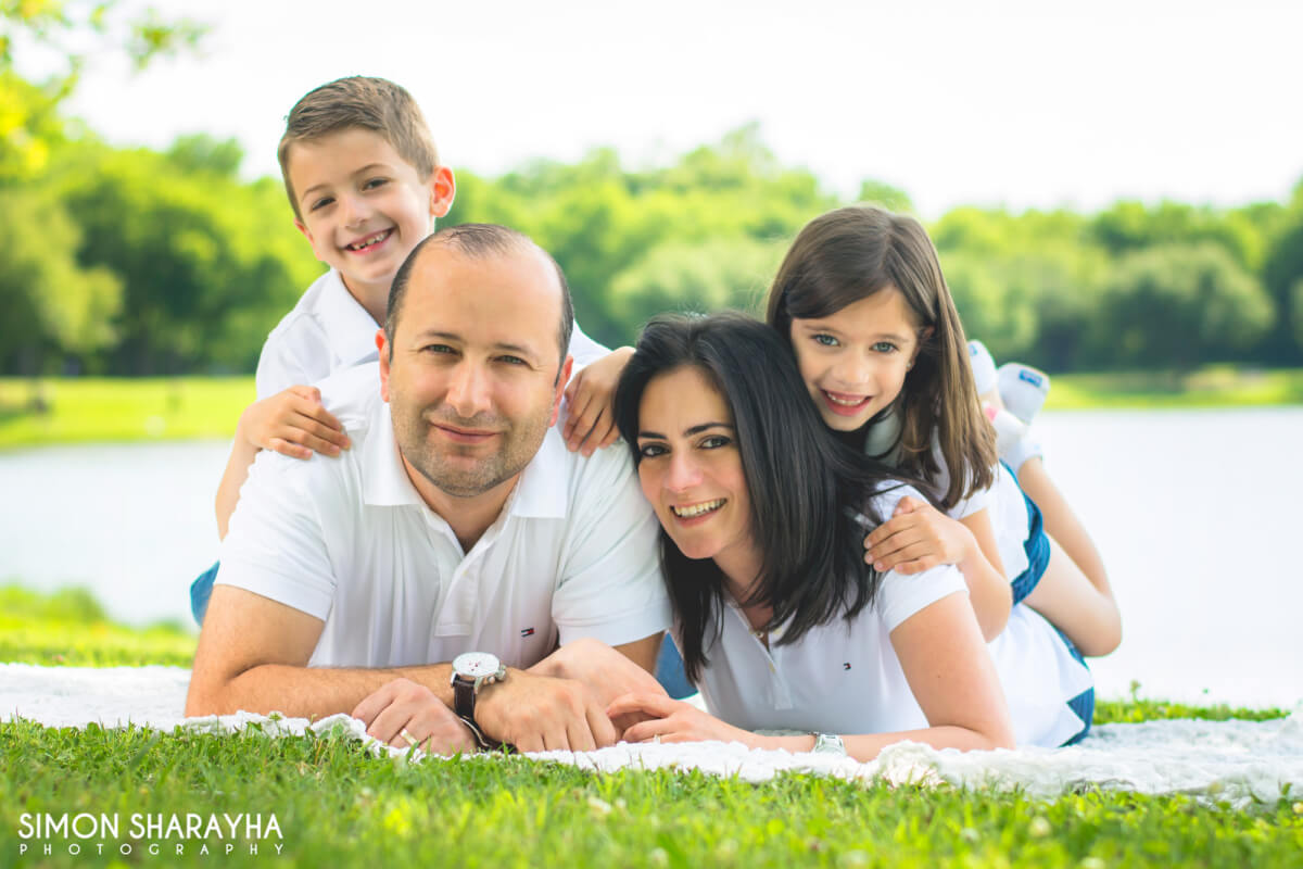 cute family posing for camera on ground grass