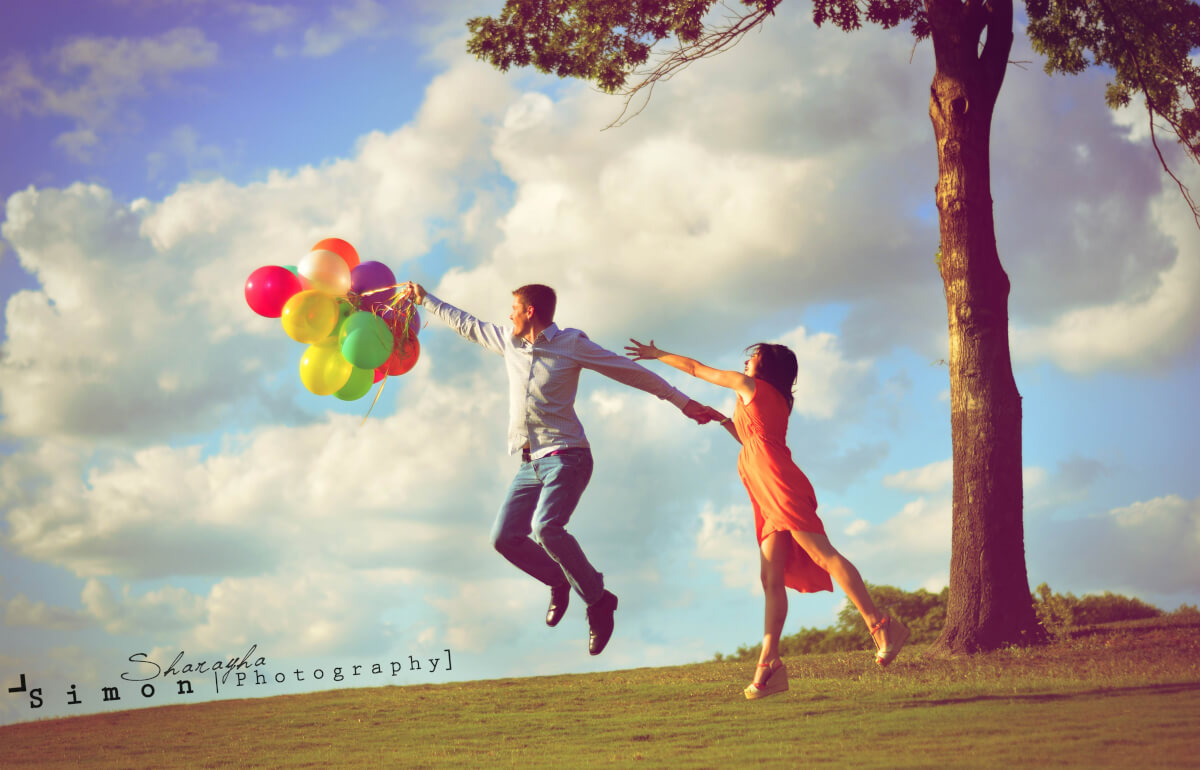 man flying with balloons holding fiance